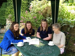 Cherish Watton sharing an issue of The Landswoman to Valerie Linder and her granddaughters.