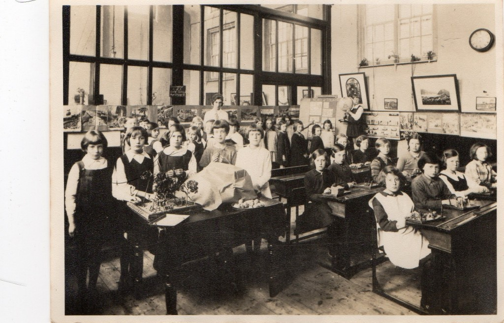 Joan and Geoff Shutte Archive Photo 23 Geoff: 'School room picture about 1933, or 1934. My mother is the 3rd from the left, standing behind the flower display. I am assuming the school room is in Dorchester, somewhere. Most likely in Coberg Road, Victoria Park, Dorchester, Dorset.'