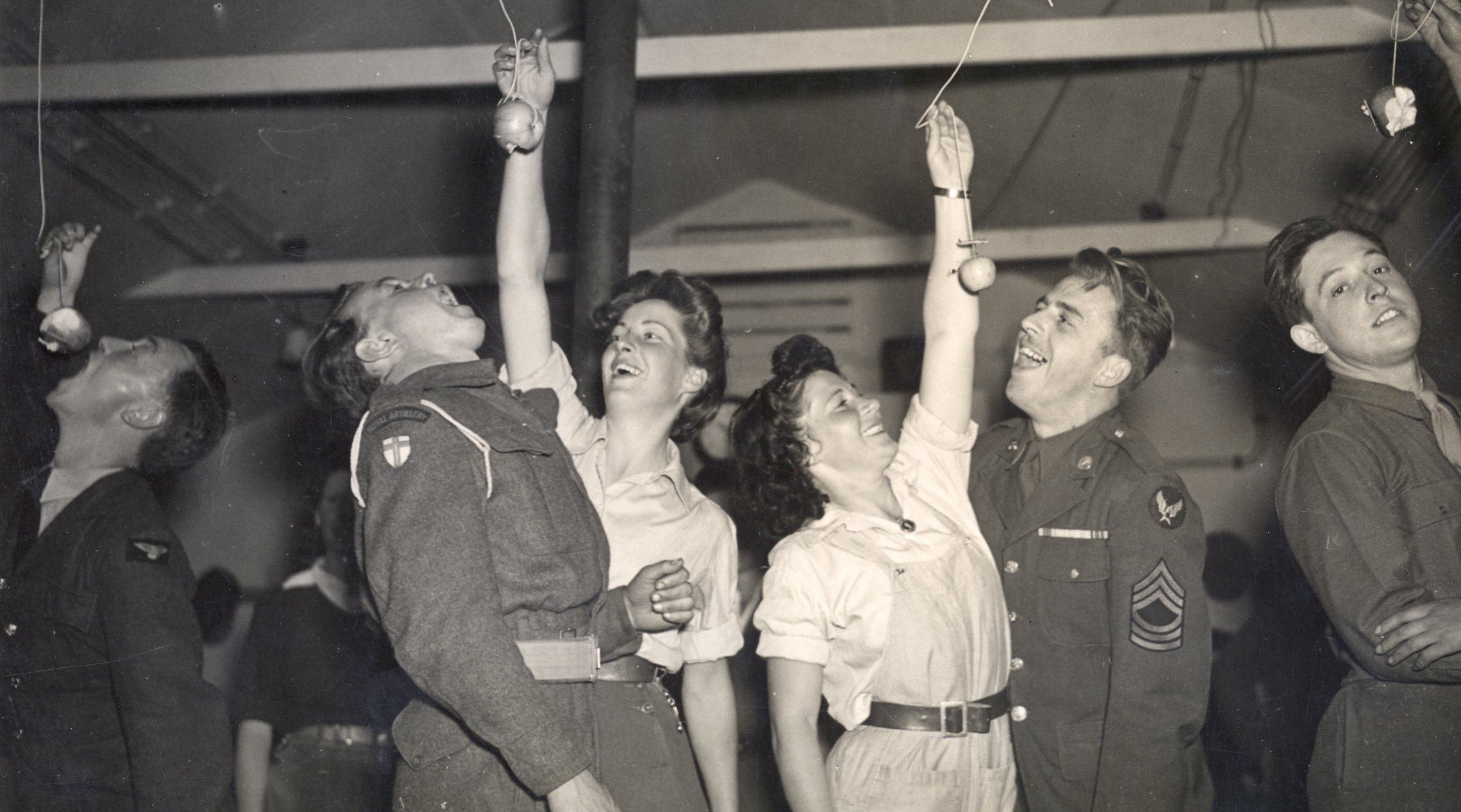 Caption: Ann Brodrick (left) with British serviceman and Mary Codrington with an American serviceman at a Halloween party c.1943 in Milton Ernest WLA hutment hostel, Bedfordshire.