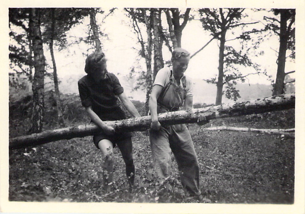 Spenny and another Lumber Jill carrying the trunk of a tree.