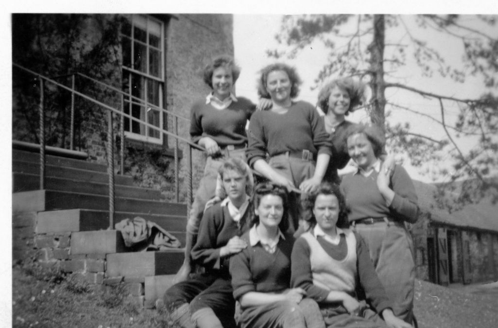 A group of Land Girls outside of a house